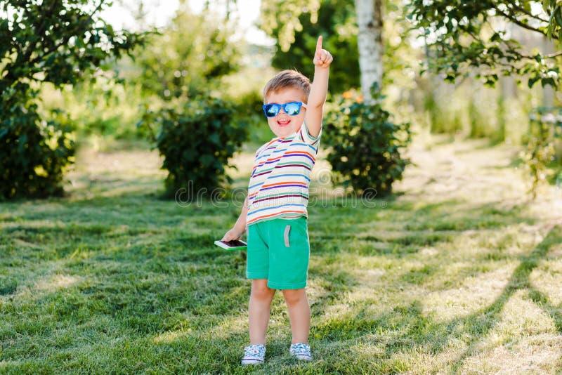 一点逗人喜爱的男孩在有他的电话的明亮的太阳镜看起来启发和愉快 免版税库存图片