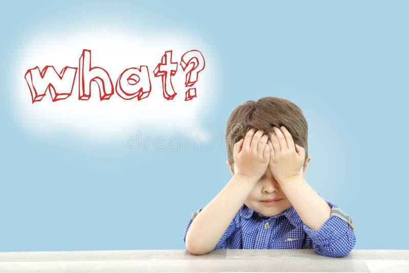 一点逗人喜爱的男孩坐并且问什么在被隔绝的背景 免版税库存照片