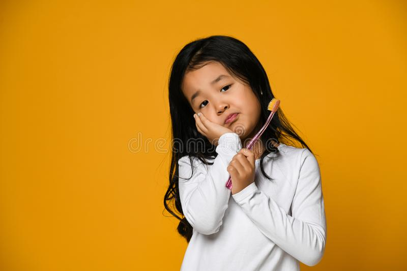 一点遭受牙痛-牙齿问题的亚裔女孩 库存照片