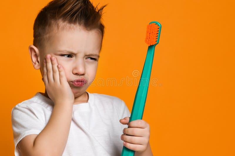 一点遭受牙痛-牙齿问题的亚裔男孩 免版税库存图片