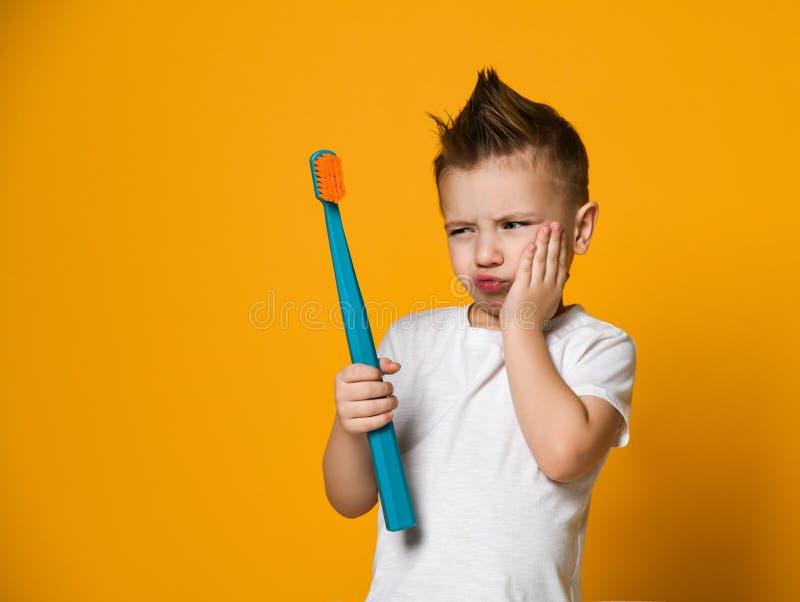 一点遭受牙痛-牙齿问题的亚裔男孩 库存照片
