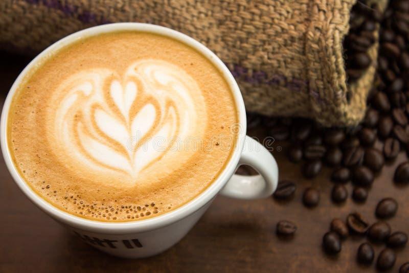 一点郁金香拿铁艺术用coffe豆和大袋 库存图片