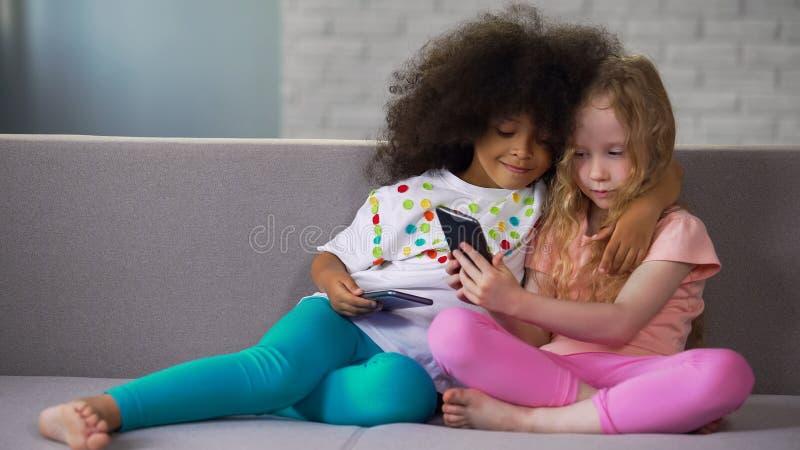 一点长沙发,拥抱和照相的不同种族的姐妹在智能手机 免版税库存照片