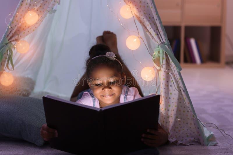 一点非裔美国人的女孩读书催眠故事在小屋 免版税图库摄影