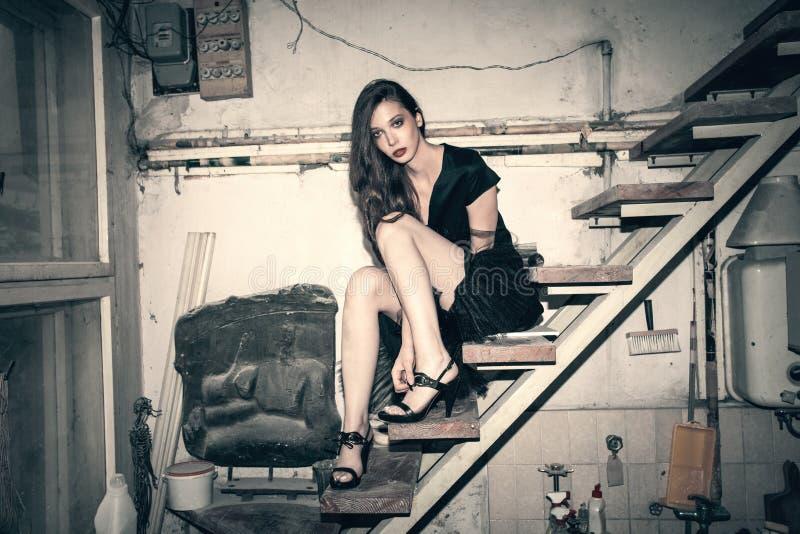 一点黑礼服的年轻时尚妇女在老艺术家演播室s 免版税图库摄影