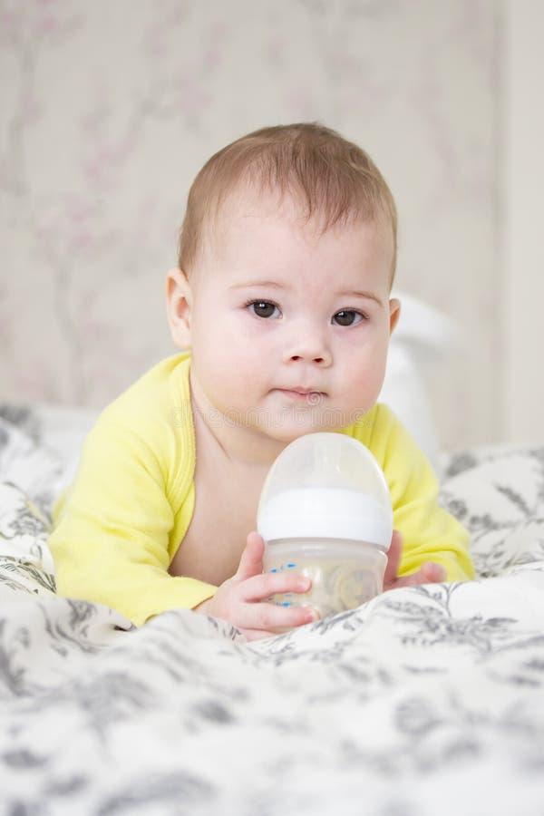 一点7个月拿着一个瓶牛奶的女婴男孩 逗人喜爱的欧洲白种人孩子以说谎在与瓶的床上的黄色, 库存照片