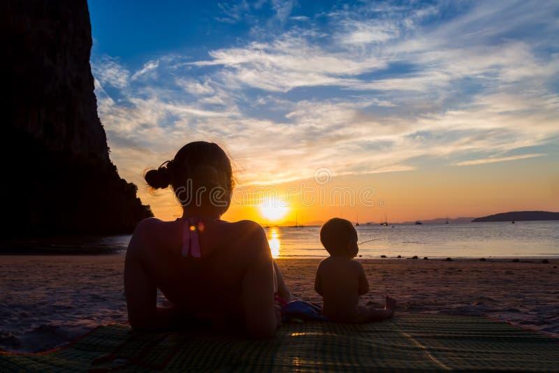 有她的女儿的母亲 一点9个月的女婴 结合坐一个热带海滩,观看并且享受日落 免版税库存图片