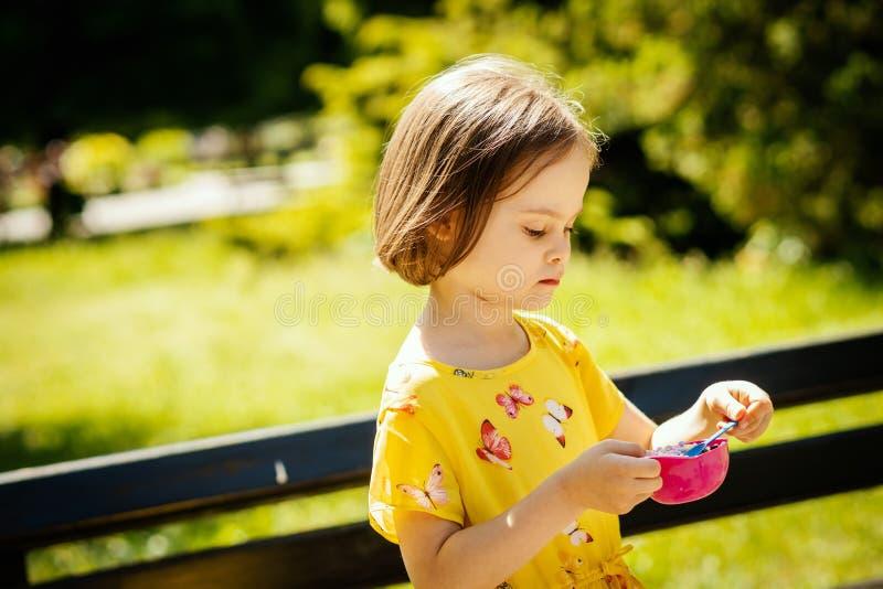 一点girll在公园吃冰淇凌在夏天 图库摄影