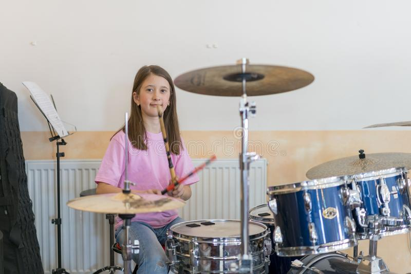 一点shuoting白种人女孩的鼓手播放elettronic鼓成套工具和 青少年的女孩获得演奏鼓集合的乐趣在音乐 免版税库存照片