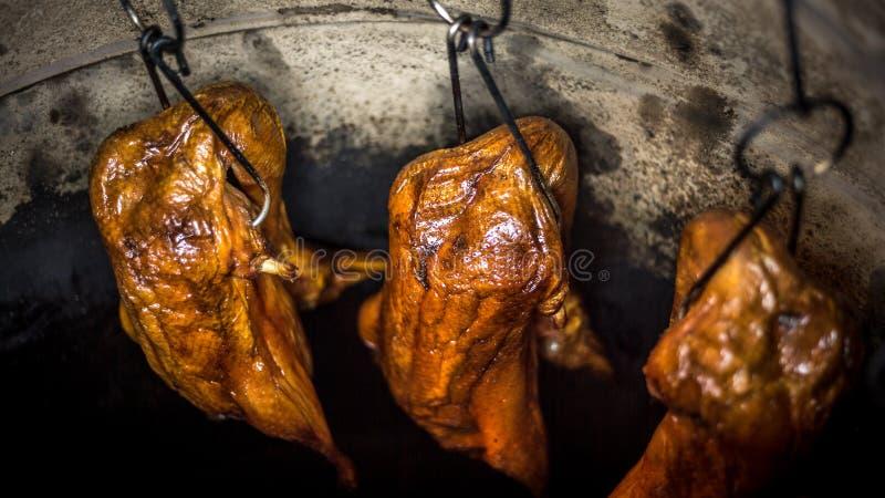 一烤鸭肉的特写镜头在一家亚洲餐馆的巨大的黏土烤箱的 库存照片