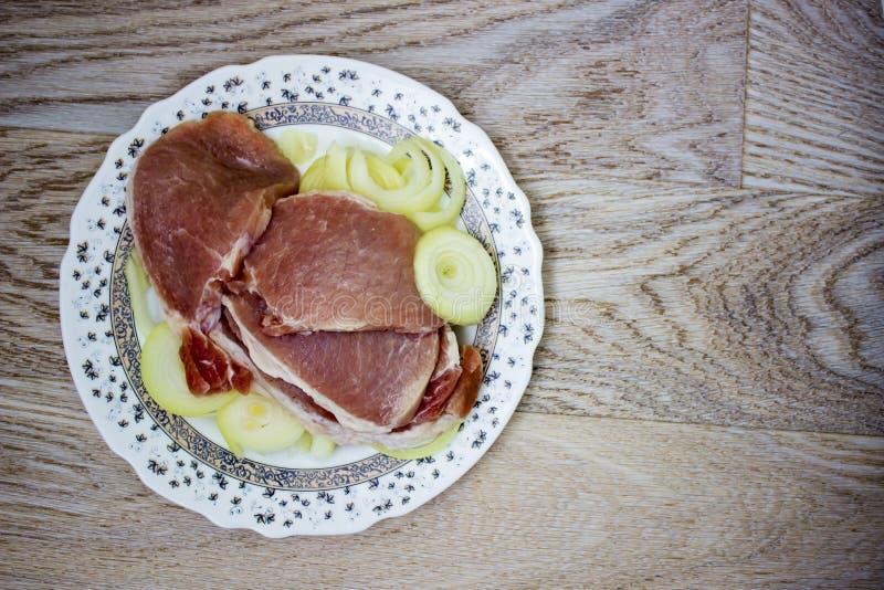 一片无骨的肉生肉和洋葱圈 免版税库存照片