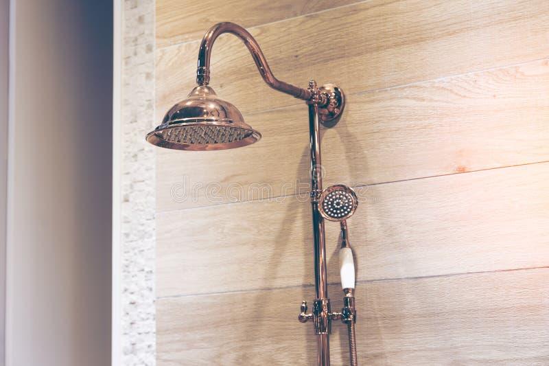 一现代淋浴喷头飞溅的图象 铜淋浴喷头,木墙壁背景 免版税库存照片