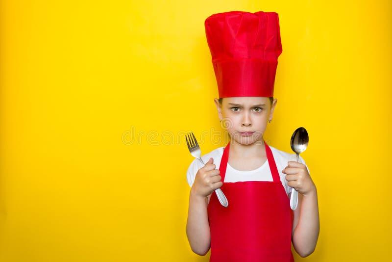 一生气少女的画象拿着一把匙子和叉子在黄色背景的一位红色厨师的衣服的与拷贝空间 免版税库存照片