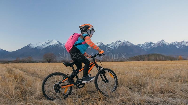 一白种人儿童乘驾在麦田骑自行车 在背景的女孩骑马黑色橙色周期美丽多雪 免版税库存图片