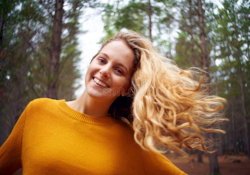 一白肤金发的年轻女人的画象有吹的头发的 免版税库存照片