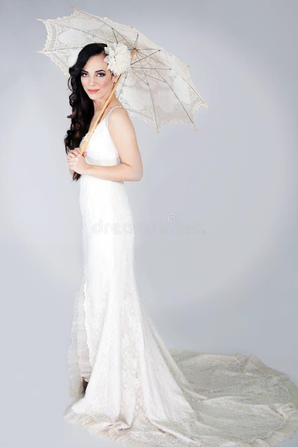 一白色婚礼礼服摆在的美丽的端庄的妇女 免版税库存照片