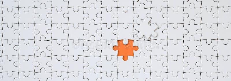 一白色拼图的纹理在一个被装配的状态的与形成橙色空间的一个错过的元素 皇族释放例证