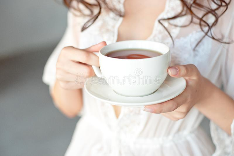 一白色杯的特写镜头与一心形的热的拿铁艺术咖啡在少女的手上 库存图片