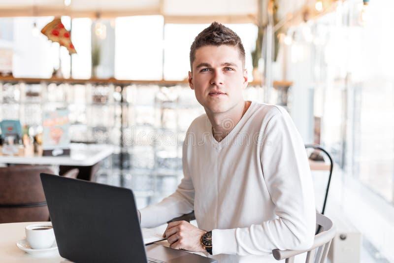 一白色衬衫的成功的年轻商人有一台现代计算机的在咖啡馆坐 遥远地工作凉快的自由职业者的人 库存图片