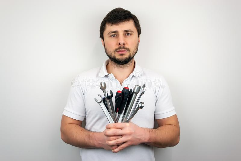 一白色T恤的一个严肃的有胡子的人人有板钳和螺丝刀花束的  图库摄影