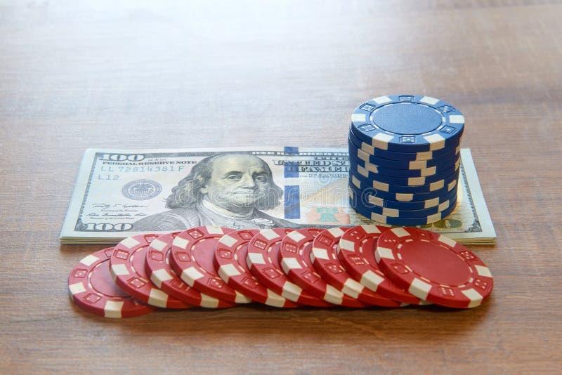 一百元钞票和纸牌筹码在木桌上 库存图片