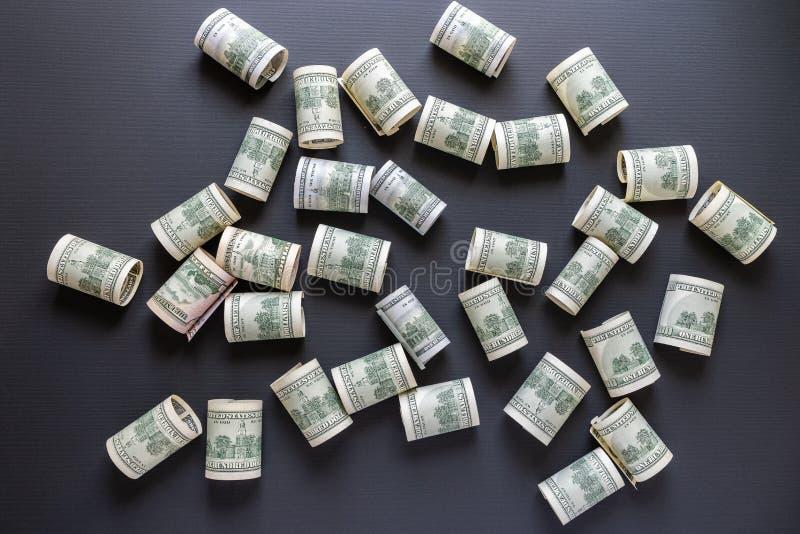 一百元钞票在黑背景,美国货币驱散 免版税库存照片