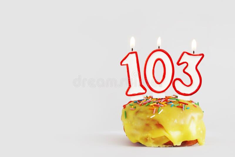 一百和三年周年 与白色灼烧的蜡烛的生日杯形蛋糕与以103数字的形式红色边界 免版税图库摄影