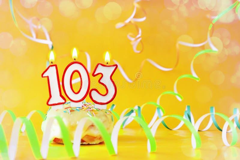 一百和三年生日 与灼烧的蜡烛的杯形蛋糕以第103的形式 免版税图库摄影