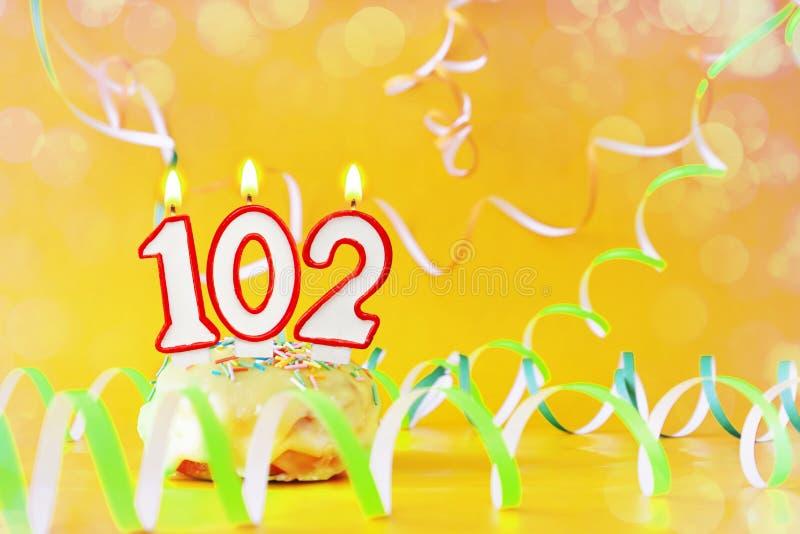一百和两年生日 与灼烧的蜡烛的杯形蛋糕以第102的形式 免版税库存图片