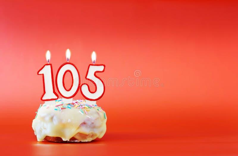 一百和五年生日 与白色灼烧的蜡烛的杯形蛋糕以第105的形式 免版税库存图片