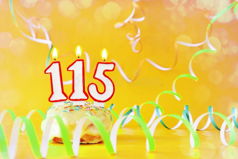 一百和十五年生日 与灼烧的蜡烛的杯形蛋糕以第115的形式 免版税库存图片