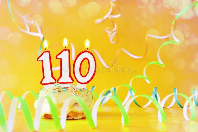 一百和十年生日 与灼烧的蜡烛的杯形蛋糕以第110的形式 免版税库存照片