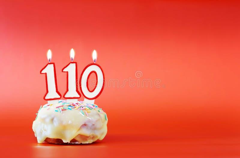 一百和十年生日 与白色灼烧的蜡烛的杯形蛋糕以第110的形式 免版税库存图片