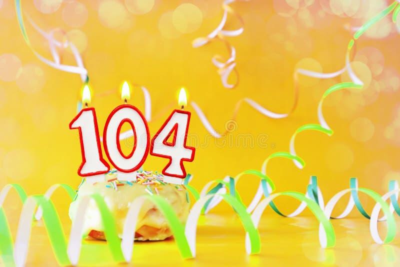 一百和四年生日 与灼烧的蜡烛的杯形蛋糕以第104的形式 免版税图库摄影