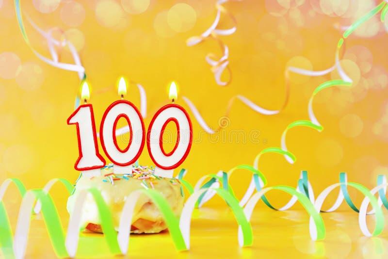 一百年生日 与灼烧的蜡烛的杯形蛋糕以第100的形式 库存照片