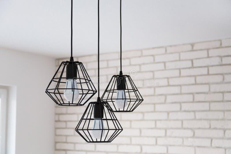 一盏现代顶楼枝形吊灯由在时髦的白色内部的黑导线制成 库存照片
