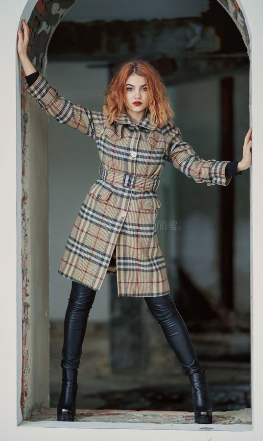 一短的方格的外套和黑紧身裤的红发少女在高跟鞋在windo的一个被放弃的房子里摆在 免版税库存图片