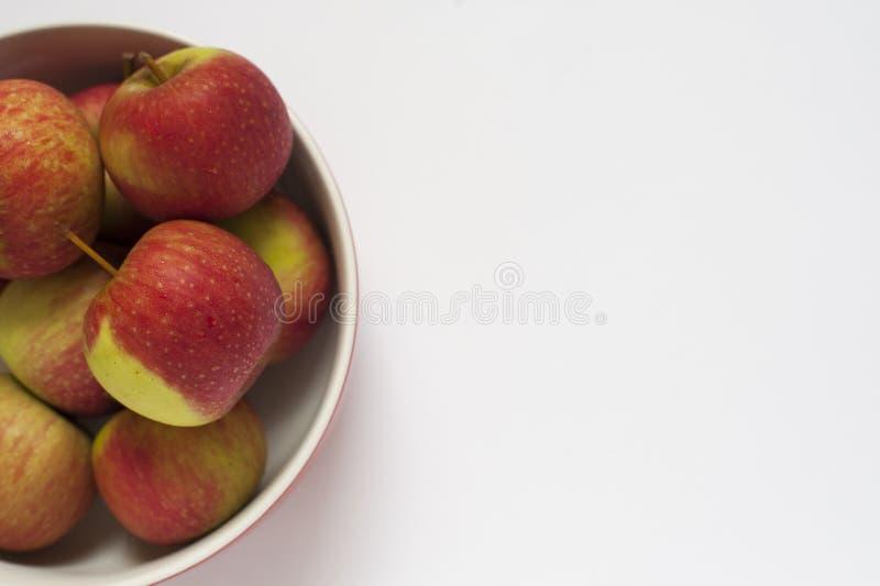 一碗在白色背景的苹果 库存图片
