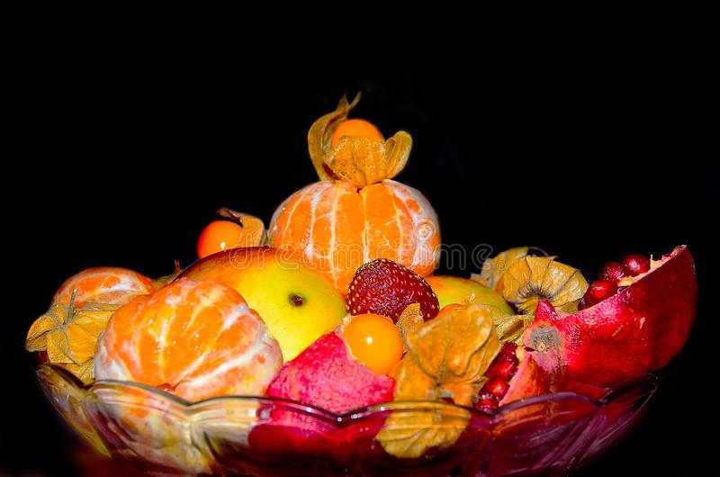 一碗在黑背景的水多的果子 免版税库存照片
