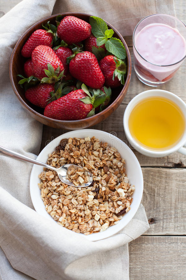 一碗自创格兰诺拉麦片用酸奶和新鲜的草莓在木背景 健康早餐用绿茶 免版税库存照片