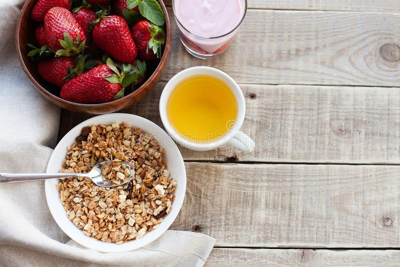 一碗自创格兰诺拉麦片用酸奶和新鲜的草莓在木背景 健康早餐用绿茶 库存照片