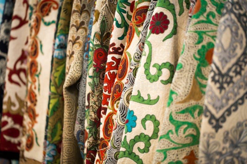 一种五颜六色的织品的特写镜头视图与一件传统东方装饰品的 手工制造,传统布料和刺绣 照亮 免版税库存照片