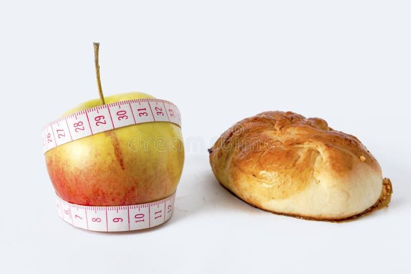 一种健康生活方式的概念 在一个红色苹果旁边的一个小圆面包 在一卷测量的磁带包裹的苹果 免版税库存照片
