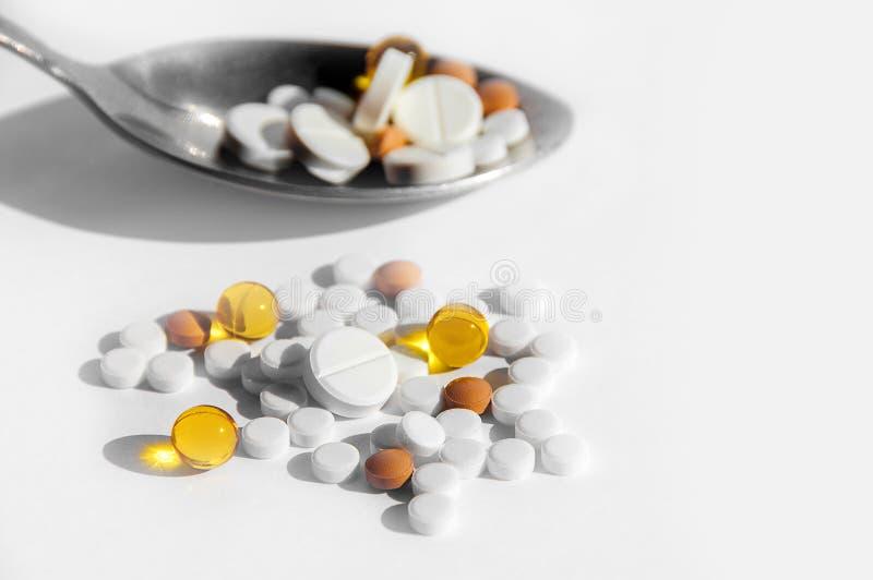 一种健康生活方式的疾病的概念,治疗和适当的营养 在一把匙子的不同的药片在轻的背景 库存照片