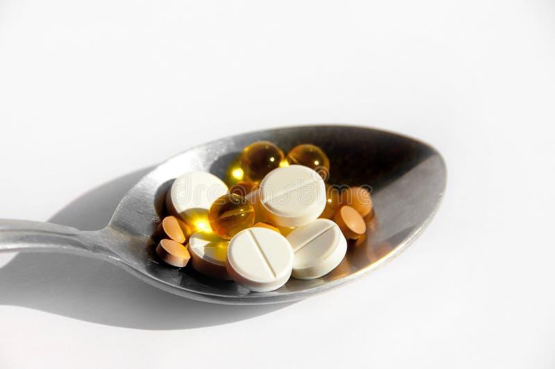 一种健康生活方式的疾病的概念,治疗和适当的营养 在一把匙子的不同的药片在轻的背景 免版税图库摄影
