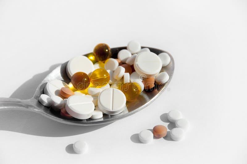 一种健康生活方式的疾病的概念,治疗和适当的营养 在一把匙子的不同的药片在轻的背景 图库摄影