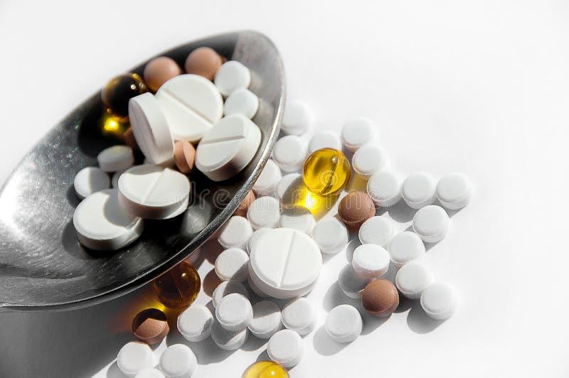 一种健康生活方式的疾病的概念,治疗和适当的营养 在一把匙子的不同的药片在轻的背景 免版税库存照片