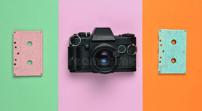 一种减速火箭的卡型盒式录音机磁带淡色和一台影片照相机在色纸背景 复制空间 最低纲领派趋向 免版税库存照片