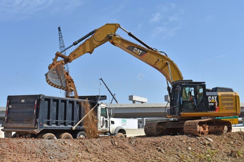 一种大挖掘机倾销土入卡车 免版税图库摄影