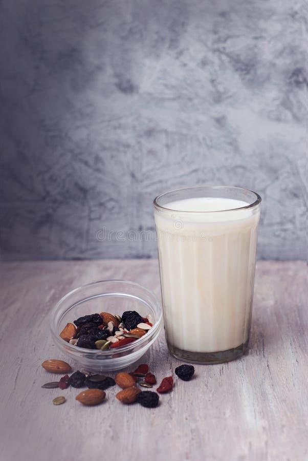 一种子的杯牛奶和混合在玻璃碗的 杏仁,葡萄干,南瓜籽,向日葵种子,核桃 健康早餐饮食 免版税库存图片